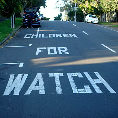 Children for watch painted road sign sign in Mt Eden, Auckland, photographed by Angle Limited